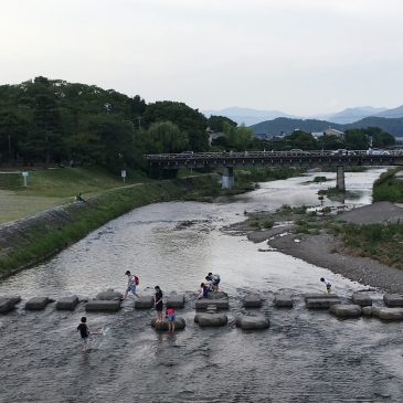 Photographer crossing the Kamoriver at Demachiyanagi, Kyoto.